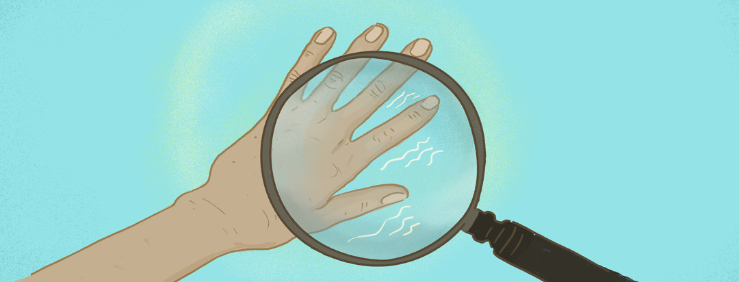 A magnifying glass hones in on a hand with a tremor.