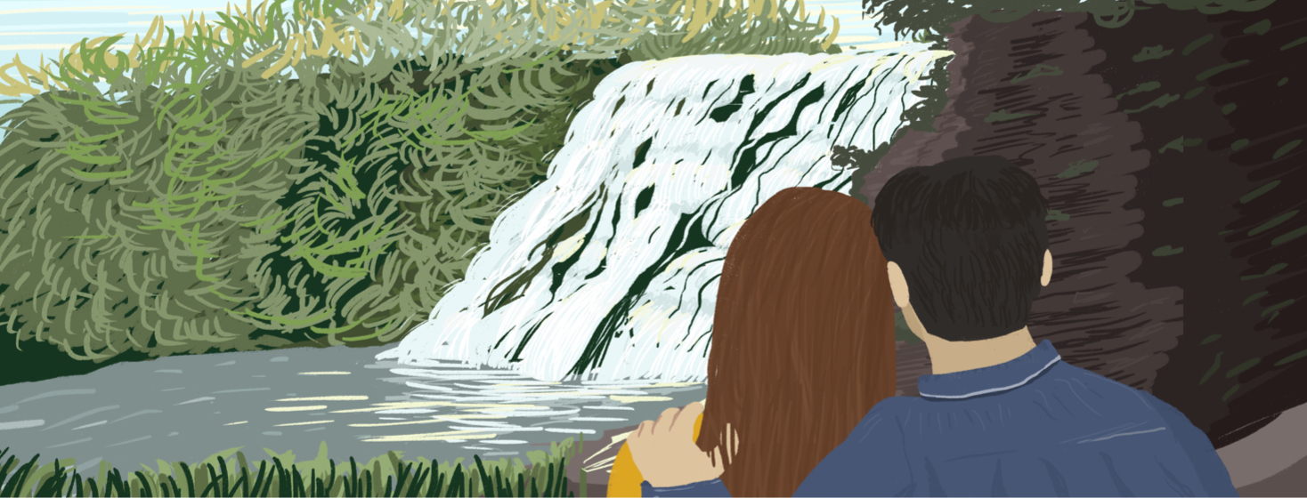 A couple wraps their arms around each other while watching the Ithaca waterfalls.