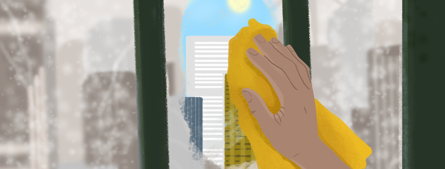 A person's hand wipes away a fogged window to reveal a patch of sunlight gleaming through city buildings.