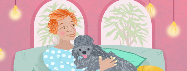 A person with red hair smiles at a fluffy gray poodle. A couch and soft lights float behind her.