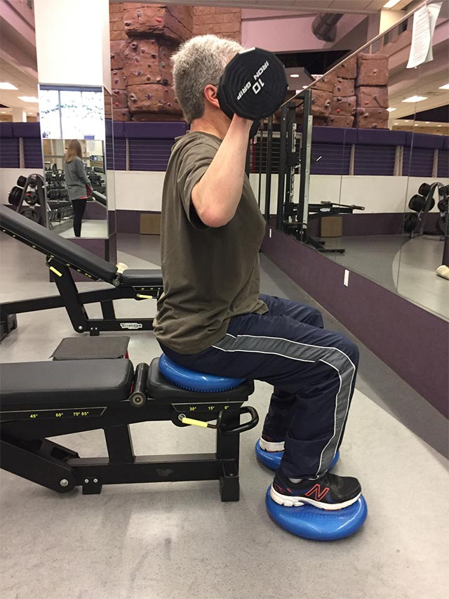 A man seated on an exercise bench lifts free weights.