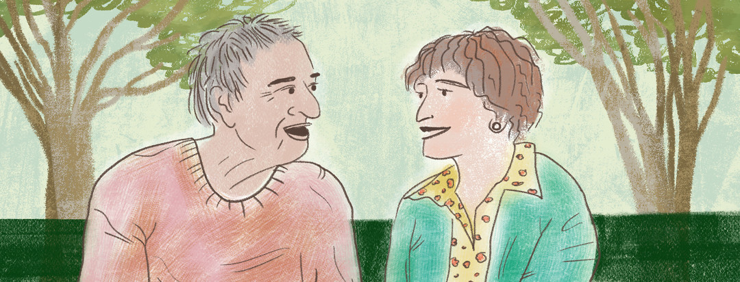 Couple sitting on bench smiling at each other; growing trees behind them.