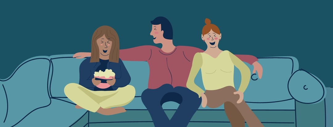 People sitting on couch with popcorn laughing and hugging.
