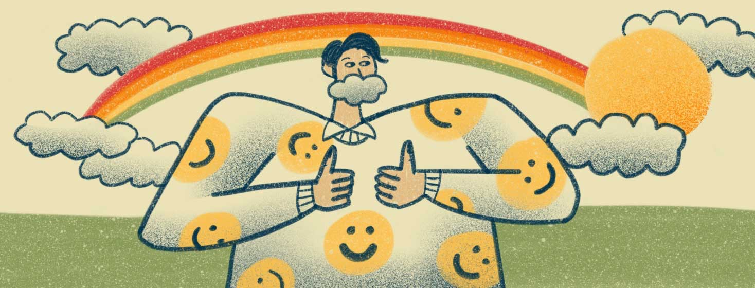 Man wearing a shirt with smiley faces and holding two thumbs up. In the background, there is a rainbow, sun and clouds.